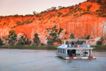 Houseboat cruising on sunset near Headings Cliffs, Riverland